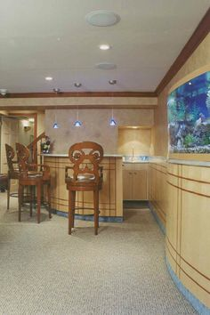 Basement bar and entertainment area.... Features a curved fish tank with all needed access to equipment in insulated garage,  and blue accents via the marble mosaic selections.