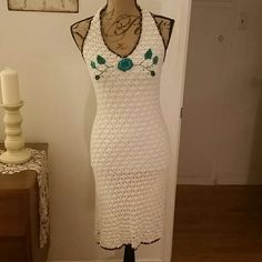 Stunning vintage crocheted dress White fully lined crochet dress.  Neck and hem brown crochet boarders.  Teal crochet and cloth flower and leaves across the bust area.  Adorned with sequins and beads on halter neckline and ties.  Also interlaced with the flowers and leaves.  All sequins intact.  Very unique, always got compliments.  Still in amazing condition.  Please ask questions before purchase.  Too many details to describe, gorgeous! Knee length. Arden B Dresses