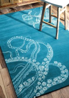 Create a cool coastal look with this gorgeous hand-tufted octopus tail rug, which is a combination of viscose and wool, to bring the soft plush feeling underneath your feet. This rug can be used with a combination of other ocean themed furnishing for an elegant cool blue look in a bedroom or a den.