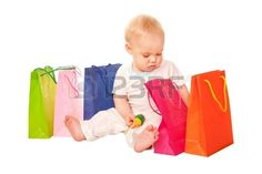 Baby shopping Happy child sitting with shopping bags examining purchase Isolated on white background Stock Photo