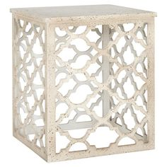 Add an eye-catching touch to your living room or den with this charming end table, showcasing an openwork quatrefoil base and distressed white finish.