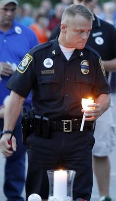 Bardstown Police Chief Rick McCubbin lights a candle at a candlelight vigil for Bardstown police officer Jason Ellis at the Bardstown Police Department. May 27, 2013