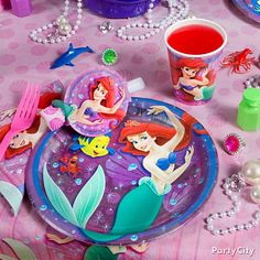 Little Mermaid Theme - Use Little Mermaid Table Covers,Plates, matching Cups, Napkins, Blowouts and a Balloon Centerpiece. Add some wow by filling a couple Purple Buckets with cut Tissue Paper to look like seaweed & Pearl Scatter & Pearl Necklaces. Then have Fish Kabobs sticking up to add some friendly faces to the table. Give each place-setting some girly love with Pink Forks,some creatures from the Sea Life Mega Pack & favors like Mini Bubbles & glamorous rings from the Girl Fun Value…
