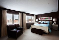 Chocolate brown walls make this large, sun-filled room feel cozy and chic. A white bed and nightstands as well as white lamps anchor the room in classic style, while a floral mural with pops of pink add visual interest.  - GoodHousekeeping.com