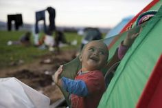 A child who is waiting to cross the Greek-Macedonian border, plays in his tent at a makeshift camp n... - Marko Djurica/ Reuters