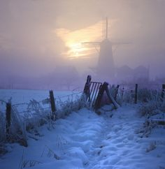 Winter windmill cloaked in mist, surrounded by twilight-blue snow.
