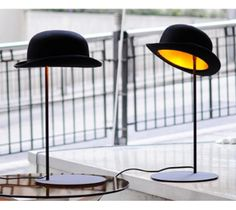 A black bowler hat table lamp called Jeeves. The outside is felt and the inside is gold to produce a warm ambient lighting, a designer table lamp. Funky Lighting, Home Lighting, Modern Lighting, Lighting Design, Office Lighting, Luminaire Design, Lamp Design, Eclectic Table Lamps, Lights