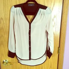 Tan and black blouse from Akira This blouse was only worn once. It has a bit of an open back but your bra is covered. The buttons are square gold. AKIRA Tops Blouses
