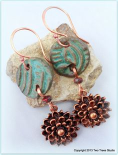 Classic meets tribal in these earrings: beautiful handcrafted ceramic disks in a rich green, copper flowers, hand-forged ear wires.  By Two Trees Studio.