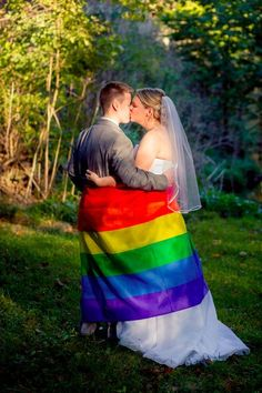 Same-sex wedding day photo idea - the two brides shared a kiss while wrapped up in a rainbow flag {Jessica Yahn Photography}