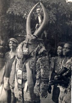 Africa | Agaba/ Mgbedike masquerade. Wearing mask and masquerade costume covered with fluffy or furry material, appliqued panels at front. Mask has long horns and sharp teeth. Small group of adult men accompanying masquerade. Man at right playing a small gong.| Photo by B. Fagg, 1946, North Nigeria