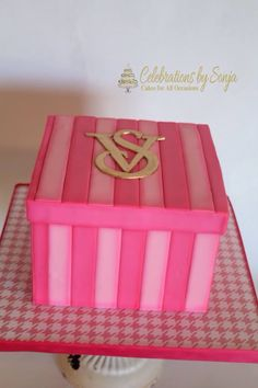 Fondant Victoria's Secret gift box cake. Vs logo is painted in edible gold paint. The gift box is airbrushed to give more dimension