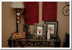 Valentine table - shutters mounted on wall at varying heights & simple red heart in frame with music paper background