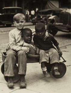Three young boys sit in a wagon on the sidewalk of a Pittsburgh neighborhood street, c. 1925