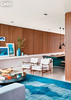 Blue and walnut mid century modern inspired living room decor // modern wood paneling walls