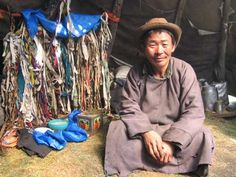Dukha Mongolian Shaman called Ganzorig sits in front of his ancestors shrine. Dukha's idols were destroyed during the communist repression. The shrine is on the North side of the wigwam which receives no sun...representing the Black Heaven portal through which his ancestors left the world f the living. The rags represent ancestors