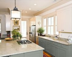 Gorgeous dark duck egg blue on the bottom cabinets with a stunning lantern over the island.