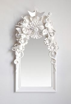 Glue random small items together, spray paint all one color and attach to mirror.