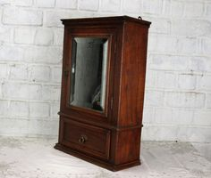 Vintage Medicine Kitchen small Wall Cabinet Apothecary wood beveled glass mirror  this lovely apothecary cabinet is 21.26(54 cm) high, 13.98 (35.5 cm) wide and 5.71 (14.5 cm) deep, the inside of the drawer is 9.84 (25 cm) high, 4.13 (10.5 cm) wide and 3.54 (9 cm) deep, the cabinet is in overall very good vintage condition, there are spots and some wear to the mirror, minor wear to the wood and a tick on top of the cabinet (for details please see pictures, the pictures are part of the…