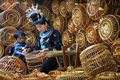 China | A woman of Miao ethnic group weaves a bird cage as a child looks on in Kala village, Danzhai county, Guizhou Province.  Approximately 90 percent of the 110 households of the local villagers live on the trade of bird cage manufacture | © Qin Gang/Xinhua Press/Corbis