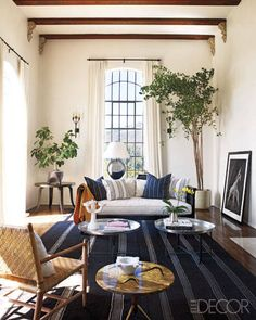 The living room of the home that actress Ellen Pompeo shares with her husband, Chris Ivery, and their daughter, Stella Luna, includes furnishings both old and new—a vintage dhurrie underfoot and a custom-made sofa by designer Martyn Lawrence-Bullard, who decorated the house.   - ELLEDecor.com