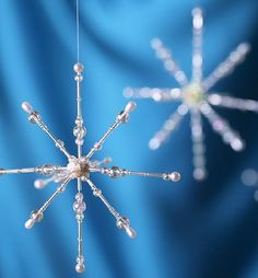 beaded snowflake ornaments made with pearl-headed corsage pins, beads and a bit of cork in the centre. 2 dozen of these. Beaded Christmas Ornaments, Snowflake Ornaments, Noel Christmas, Christmas Snowflakes, Christmas Crafts For Kids, Christmas Projects, Holiday Crafts, Beaded Snowflake, Christmas Decorations