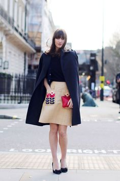 What a pretty skirt with printed pockets, paired with a navy topper swung over the shoulders. #LFW