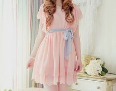 I really like the scalloped hemline on the pastel pink dress with the lilac purple ribbon around the waist.