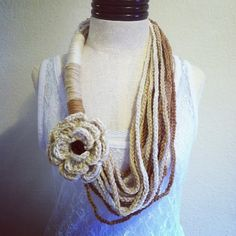 One of a kind chain/wrap scarf necklace in off white, buffalo and warm brown colors. Comes with a detachable flower that can be used as a pin or hair clip. Made with 100% acrylic yarn from the USA. Hand wash in lukewarm water only, lay flat till dry and do not iron. This item can be custom made in a variety of colors that have not been chosen yet. Price reflects length, style, yarn fibers chosen and accessories. Please refer to price list attached to original posting found in my album $46.00