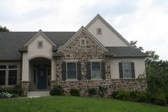 Custom home with stone veneer, board and batten shutters, and a blue front door.
