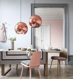 mur peinture gris clair dans une salle à manger féminine, table et chaises en bois, chaise rose et suspensions boules rose gold