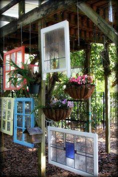comment aménager son jardin avec des vitrages et des pots suspendus avec des fleurs roses et lilas