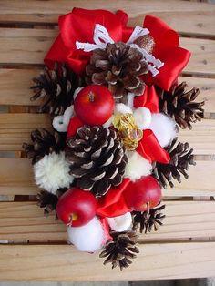 クリスマスレッドの松ぼっくりのスワッグ。松ぼっくりや木の実の間に、リボンやりんご、毛糸など異素材のものを入れています。ぽってりと丸っこい感じが温かい印象ですね。