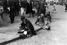 Warsaw, Ghetto Poland, Beggars sitting on the sidewalk,1941. One of the photographs taken by the German photographer Willi George over the course of a single day in the summer of 1941. The photographs are unique in that they were not staged, but showed the ghetto as it truly was