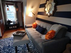 Mid-century modern living room.  Navy stripes.  Brown tweed sofa.  Coffee Bar.  Rug and sofa from Urban Outfitters.
