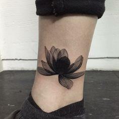 tatuaggi sulla caviglia, un fiore di loto particolare con dei petali neri aperti