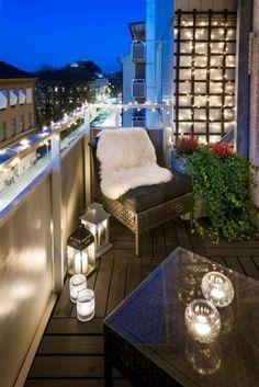 balcon-fleuri-chaise-grise-housse-en-fausse-fourrure-guirlande-lumineuse-plante-verte-bougies-allumées