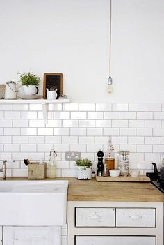 White farmhouse sink, white tiles, butcher block counter...love