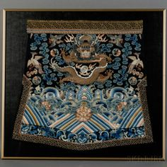 Framed Embroidery Fragment, China, Qing Dynasty (1644-1912), originally part of robe, the panel with a gold-couched, front-facing dragon encircling a flaming pearl amidst clouds and floral roundels, flanked by birds of rank embroidered in Peking knot stitch, all above a lishui border with peonies and ruyi floating in the rolling waves, hem with a floral band embroidered in three shades of blue, wan-fret brocade border added later, 24 x 26 in.