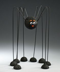 "DADDY LONG-LEG SPIDER. Supplies needed: Styrofoam balls - four 1-1/2"", one 2-1/2"" and 1"" thick scrap; clothes hangers - 8 or 16-inch lengths of wire; black acrylic craft paint, googly eyes 3/8"", craft glue or low-temp glue gun, scrap of orange felt. Also serrated knife and old candle or bar of soap; paintbrush, scissors, wooden skewers or chopsticks, wire cutters and pliers (optional)."