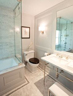 Courtney Hill Interiors- guest bathroom design w/ marble washstand, gray walls, decorative wall panels, frameless glass shower,  marble shower surround and white carrara marble hexagon floor tiles