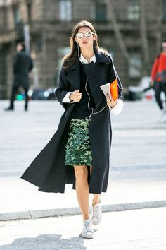 A sequined skirt is worn with a collared shirt, sweater, a duster coat, and sneaks.