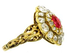 Ruby and diamond cluster ring, ca. 1840. Four larger cushion-cut diamonds set at the four corners with smaller cushion-shaped old mine cuts to outer border. Inner border set with small cushion-shaped old mine-cut diamonds. Twenty-four diamonds in total with an approximate total weight of 1.95 ct. Cushion-shaped old mine-cut ruby to centre, with an approximate weight of 0.50 ct. All in yellow gold with intricately carved shoulders.