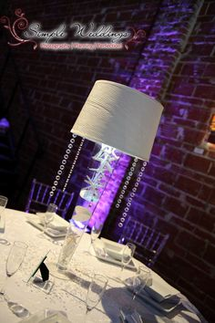 Lampshade lighted centerpiece with starfish and sand dollars. Design by Desiree Munera, Simple Weddings.