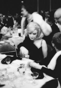 """I rarely analyse photographs of Marilyn but this photograph is so significant. At the Actor's Studio benefit at Roseland Dance Hall in March 1961, Marilyn is appearing at an event that she believes in but she is still out of place. The world is a blur and everything is happening around her, never truly for her. """"It's terrible to be lonesome especially in the middle of a crowd."""""""