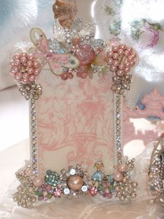 How Sweet, full of wonderful findings old and new to create a One of a Kind Jeweled picture frame for your cherished photos and bring back dear memories. (Don't buy it...DIY.  Just gather together old jewelry you wouldn't be caught dead in and earrings with one missing, etc. and glue them to a picture frame with strong glue like E-6000.  I'm totally doing this!)  Don't bother clicking on picture.  It sends you to selling sight but it is a doable idea.