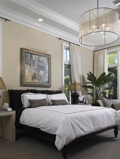 Designer Troy Beasley uses a blend of black and white in this formal bedroom. The bold contrast of the white comforter against the black sheets is an eye-catching duo.