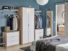 A bedroom with a wardrobe in oak effect with white doors combined with two chest of drawers also in oak effect and white.