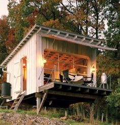 An aluminum and glass garage door opens to a cantilevered wooden deck, where a r. An aluminum and glass garage door opens to a cantilevered wooden deck, where a removable canvas awning offers shade and shelter. Tiny House Cabin, Tiny House Living, Tiny House Design, Off Grid Tiny House, Small Tiny House, Small Homes, Tiny House Movement, Canvas Awnings, Glass Garage Door
