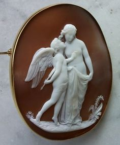 """First Whisper of Love"", ca. 1860, England. Sardonyx Shell, 15K gold tested.  Setting/pin appears to be updated. 2 2/8"" by just over 1 6/8""; signed by J. Ronca, cameo cutter to Queen Victoria. Inspired by a sculpture of the same name by Scotsman William Calder Marshall, made in 1846 for the International Exhibition of 1851 in London.This is an unusual  depiction of Cupid and Psyche. James Ronca learned the art of carving from his Italian father."